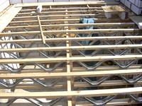 Vakwerkliggers uit hout gecombineerd met metaal als vloerconstructie.